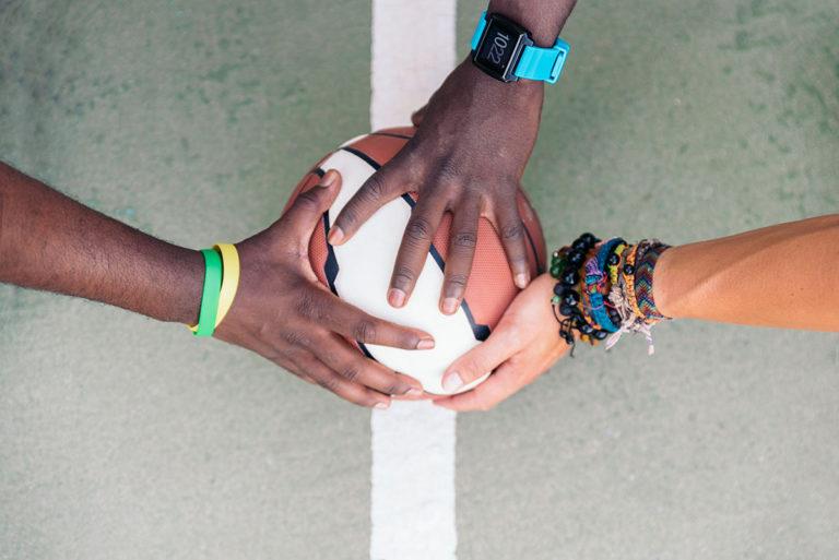 multiethnic-friends-stacking-hands-6DA3LAW